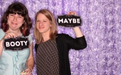 "Erin, with a questionable expression and holding a glass of champagne and a sign that says ""Booty,"" and Eve, holding a sign that says ""Maybe"""