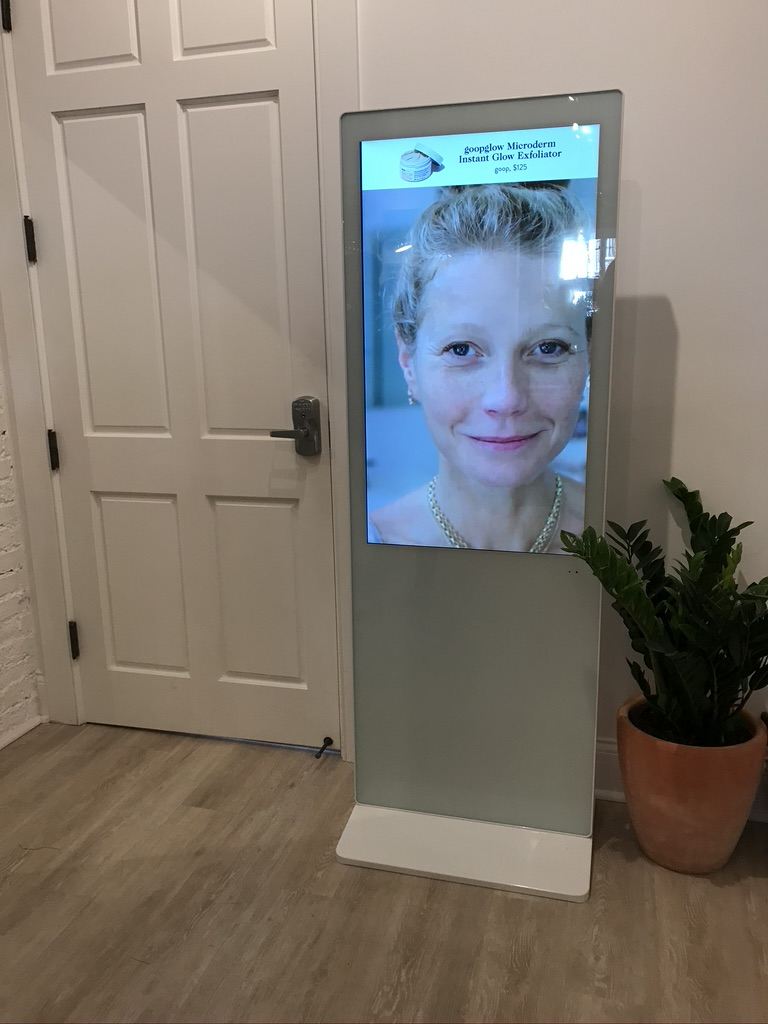 a giant screen of gwneyth paltrow next to the door of the interior of the  goop store